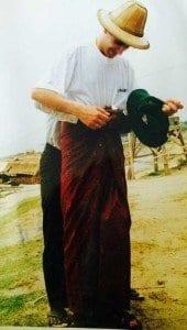 Un birmano ayuda a un viajero a colocarse un longhi