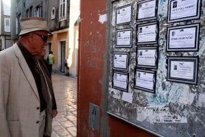 Señor leyendo las esquelas en un tablon en la calle, en Zadar