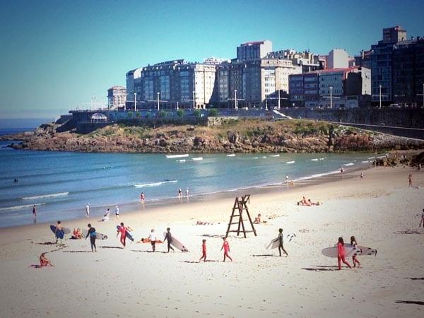 Niños haciendo surf en la playa de Riazor en La Coruña