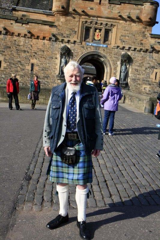 Un guia ataviado con el típico kilt escocés a las puertas del castillo
