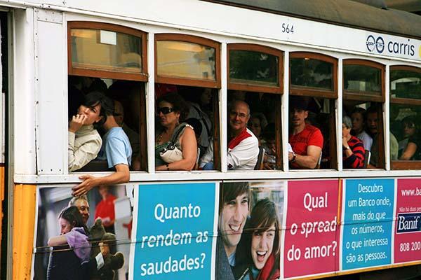 Tranvia de Lisboa con gente y carteles de publicidad