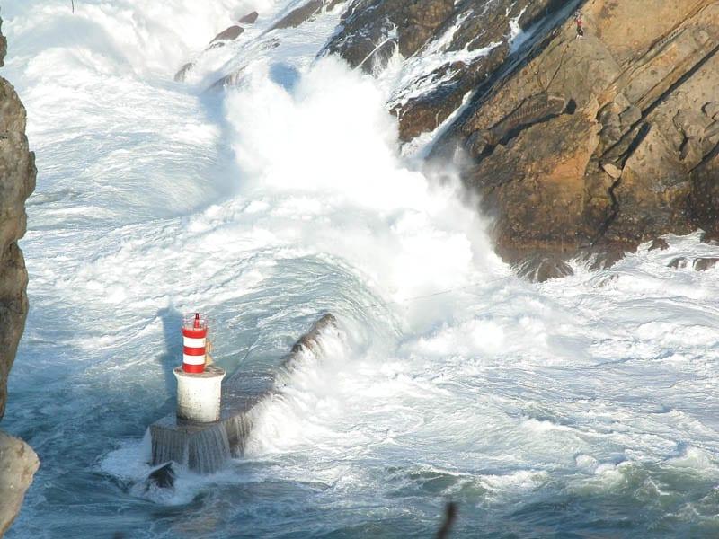 Un faro comido por las olas durante un temporal