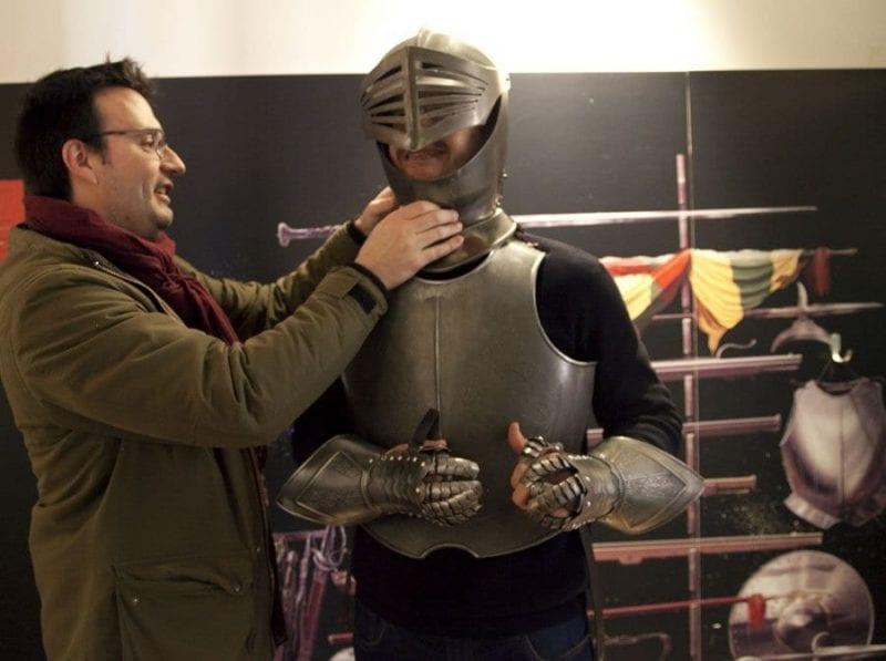 Visitantes probando la armadura de Don Quijote en el museo del Hidalgo