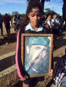 Niña con iuna foto de Fidel Castro el día de su muerte