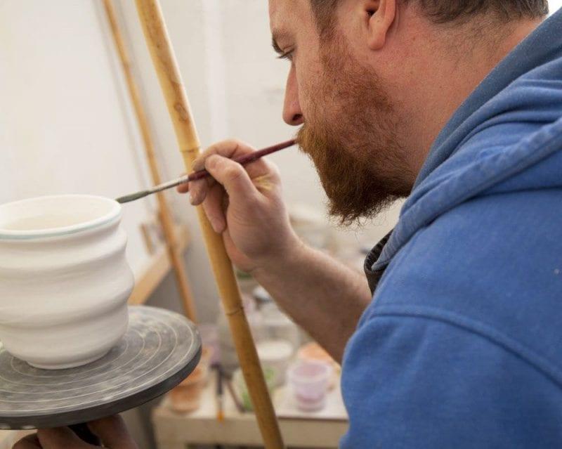 Gustavo del Pino pintando con la ayuda de una caña