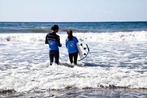 Un monitor con su alumna en una clase de surf