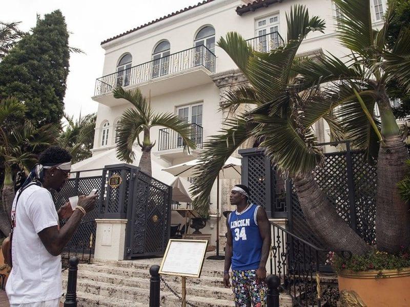 Dos turistas haciéndose fotos ante la mansión de Versace