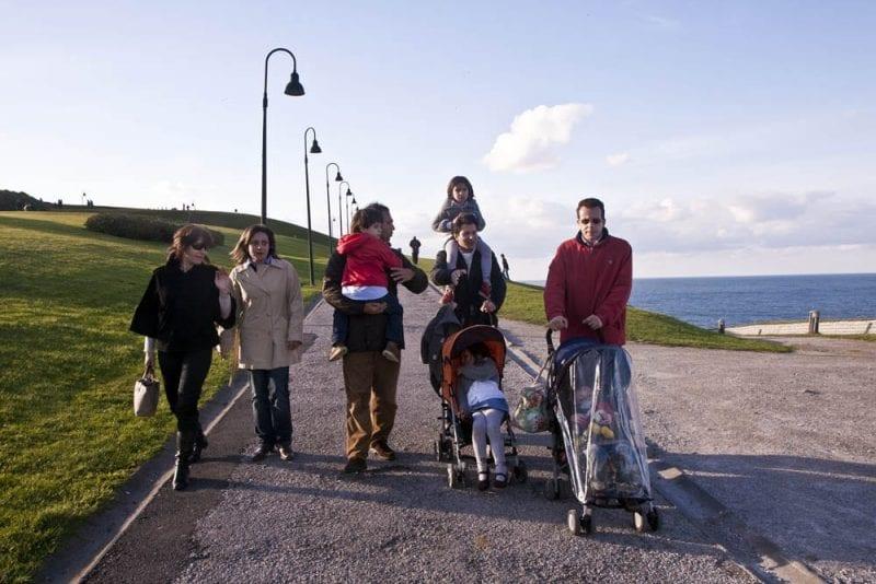 Un grupo de familias con niños paseando por Gijón