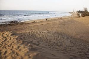 Playa con el faro de Maspalomas al fondo